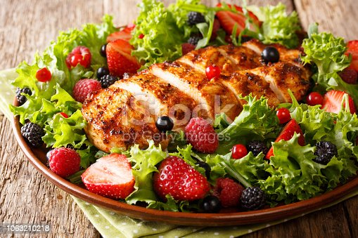 Colorful salad of grilled chicken with summer berries and herbs closeup on the table. Dietary food. horizontal