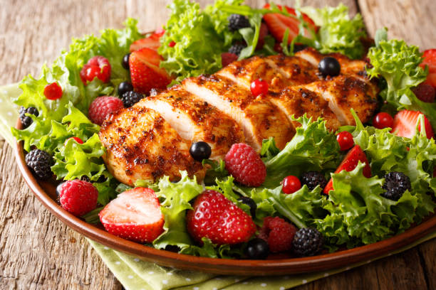 Colorful salad of grilled chicken with summer berries and herbs closeup. Dietary food. horizontal stock photo