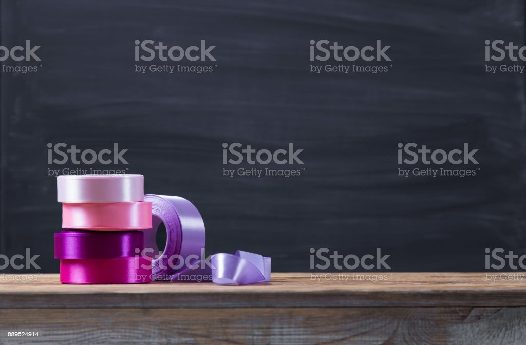 A colorful satin ribbon in a rolls on a wooden table, with abstract dark background and copy space. stock photo