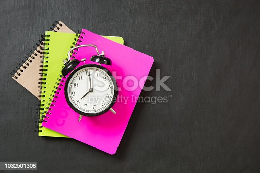 istock Colorful school supplies and alarm clock on black chalkboard. Top view, flat lay. 1032501308