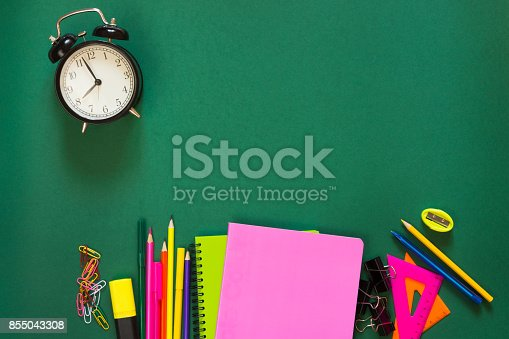 1139289535 istock photo Colorful school supplies, book, and alarm clock on green. Top view, flat lay, copy space. 855043308