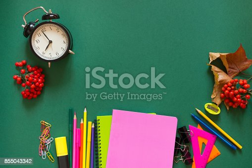 1139289535 istock photo Colorful school supplies, book, and alarm clock on green. Top view, flat lay, copy space. 855043342
