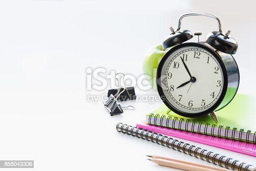 istock Colorful school supplies, book and alarm clock on white. Close up. Back to school. 855043306