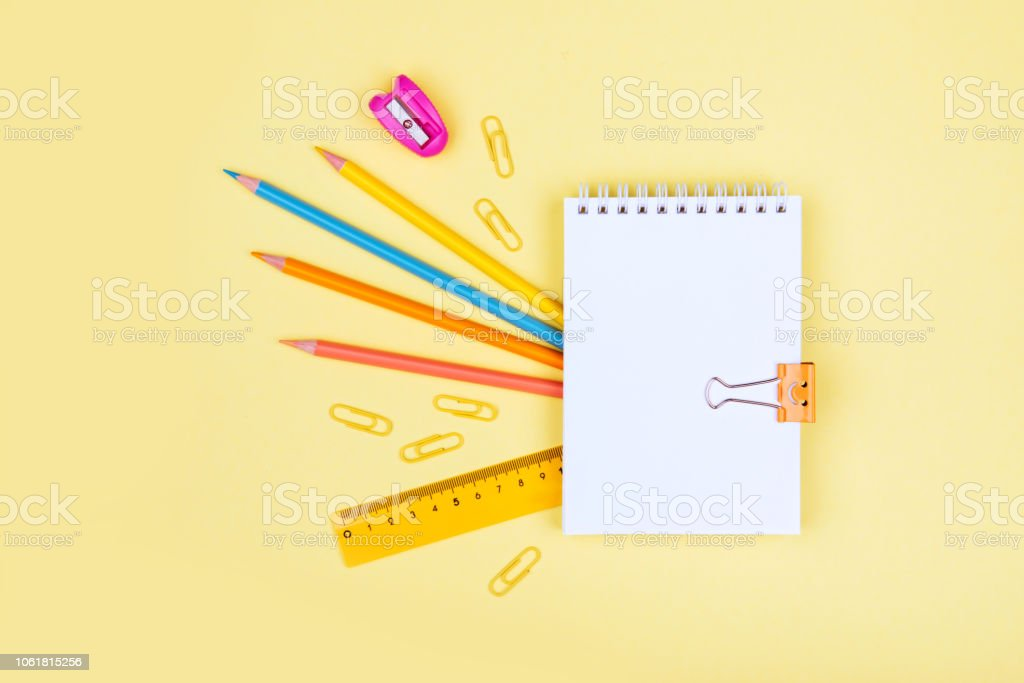 colorful school supplies on yellow background stock photo