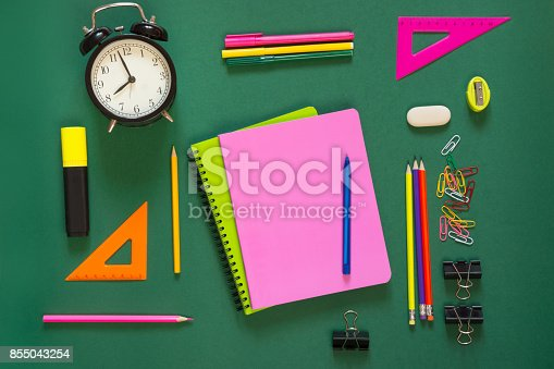 1139289535 istock photo Colorful school supplies, pink book and alarm clock on green. Top view, flat lay, copy space. 855043254