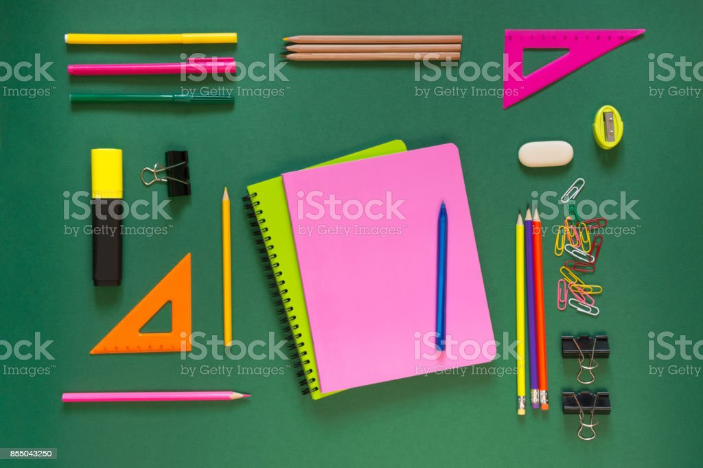 Colorful school supplies, pink book on green. Top view, flat lay, copy space. royalty-free stock photo