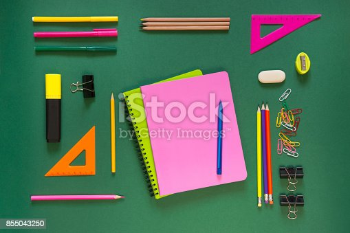 istock Colorful school supplies, pink book on green. Top view, flat lay, copy space. 855043250