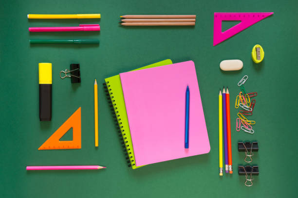 Colorful school supplies, pink book on green. Top view, flat lay, copy space. Colorful school supplies, pink book on green background. Top view, flat lay, copy space. workbook stock pictures, royalty-free photos & images