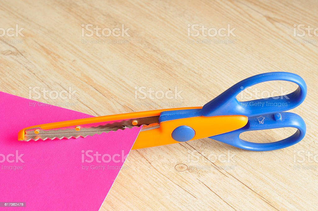Colorful scissor that cut a zigzag pattern stock photo