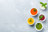 Healthy food, clean eating concept. Variety of colorful seasonal fall vegetables creamy soups with ingredients. Pumpkin, broccoli, carrot, beetroot, potato, tomato spinach. Flat lay, copy space