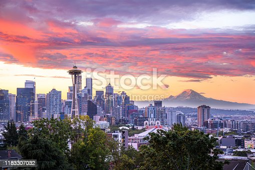 Colorful sunrise over Seattle, WA. An orange pink sky contrasts with the hazy blue early-morning glow of the city. Mt Rainier can clearly be seen in the distance.