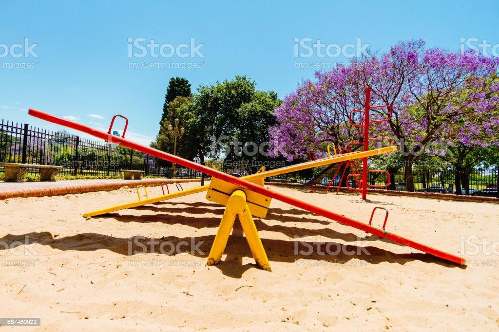 Balancín de colores visto desde el lado en el arenero de un parque - foto de stock