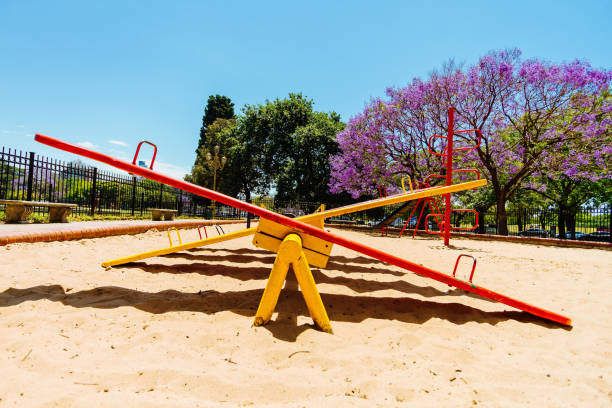 Colorful seesaw viewed from the side in the sandbox of a park stock photo