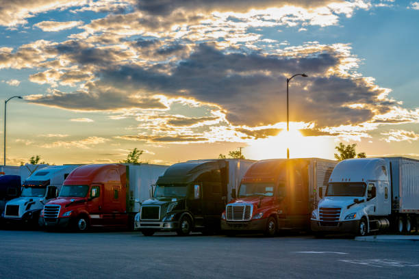 Colorful Semis Closely Parked Side By Side In A Parking Lot With A Beautiful Colorado Sunset Behind Them stock photo