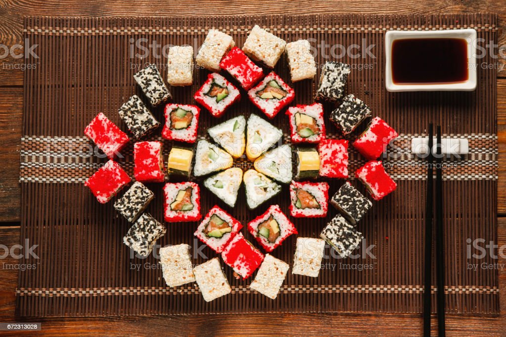Colorful delicious set of sushi served on brown straw mat, flat lay....