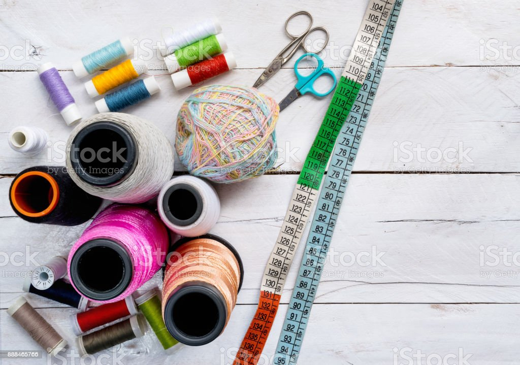 Colorful Sewing thread line spools, big and small, scissors, and measuring tape on top of a white wooden background tabletop, concept and idea stock photo