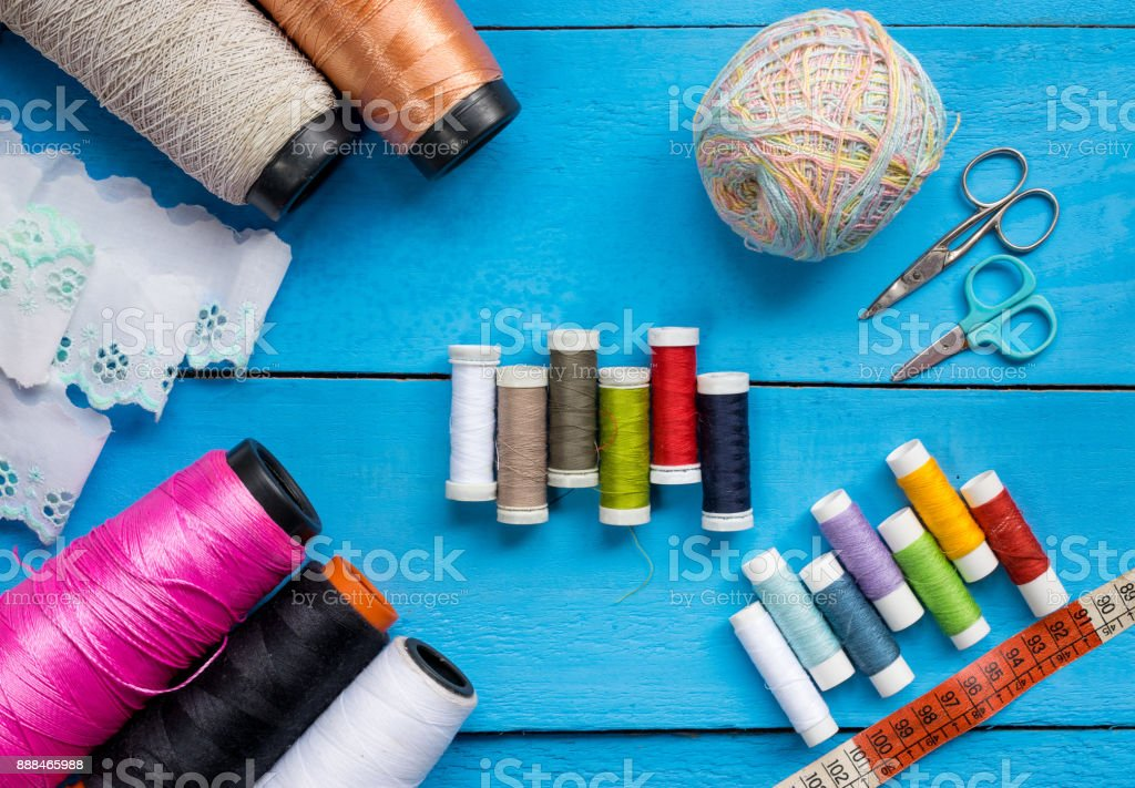 Colorful Sewing thread line spools, big and small, scissors, frill soft cloth and measuring tape on top of a blue wooden background tabletop, concept and idea stock photo