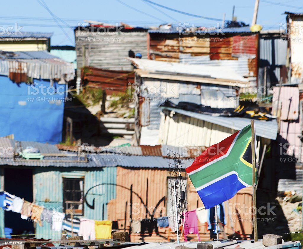 Colorful shacks with washing line and South African flag royalty-free stock photo