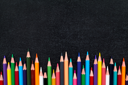 istock Colorful sharpened pencils in a row on blackboard 596780300