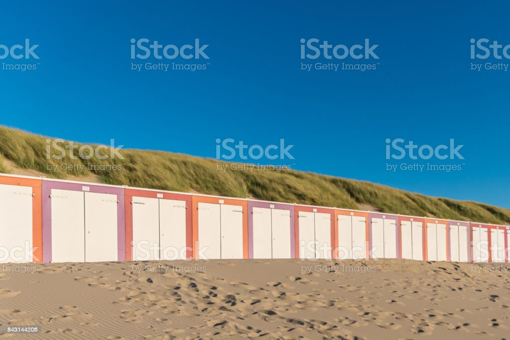 Colorful sheds at the beach in front dunes during sunset stock photo