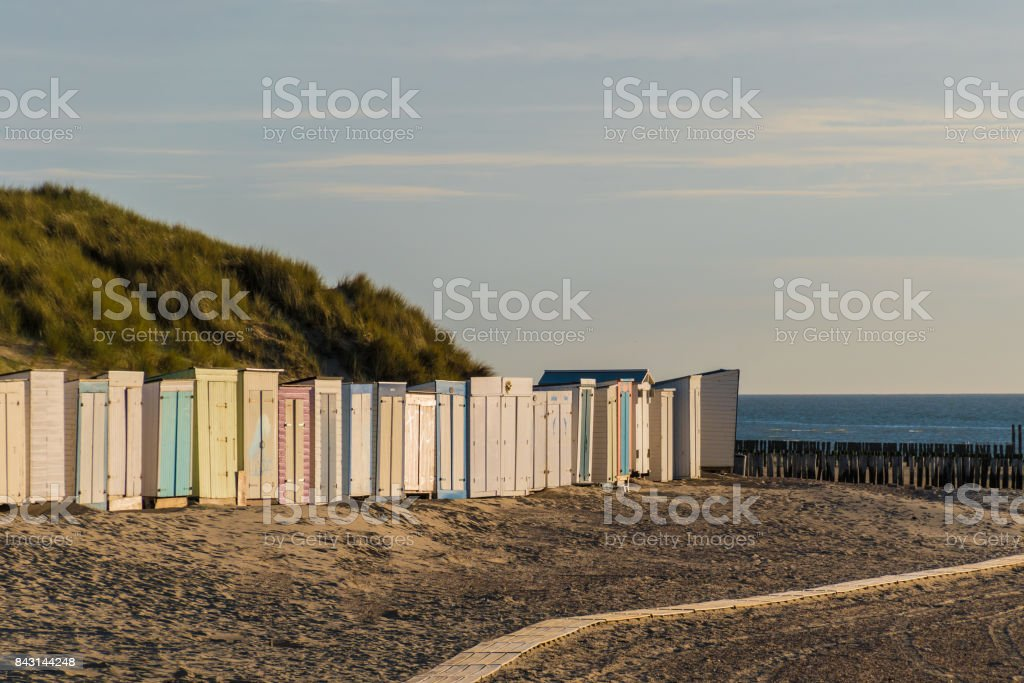 Colorful sheds at the beach in front dunes sunset stock photo