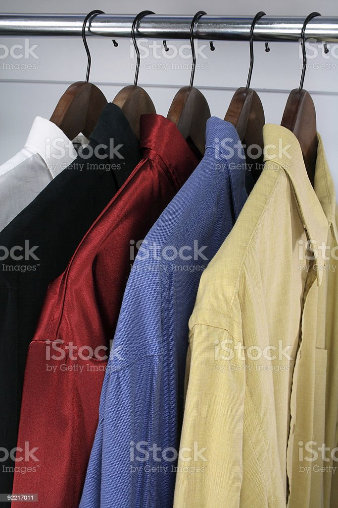 Colorful shirts on wooden hangers royalty-free stock photo
