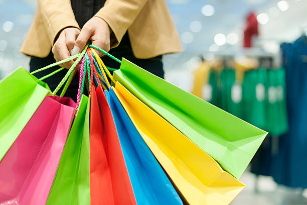 Colorful shopping bags being held on blurry mall background Woman with shopping bags large group of objects stock pictures, royalty-free photos & images