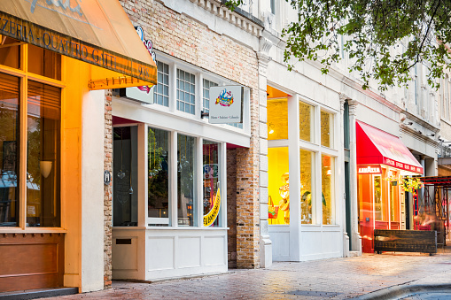 Photo of a row of illuminated, colorful shops, restaurants and businesses on Congress Avenue in Downtown Austin, Texas, USA.
