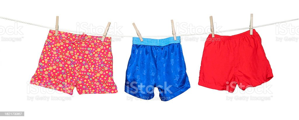 Colorful shorts hanging on a clothesline on white background stock photo