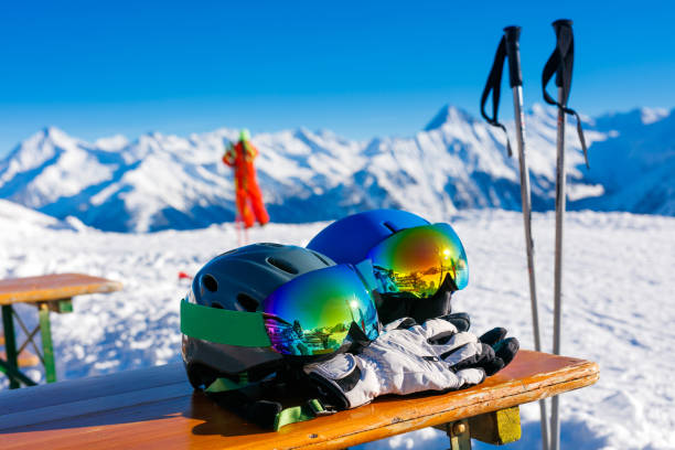 Colorful ski glasses, gloves and helmet on wooden table. stock photo