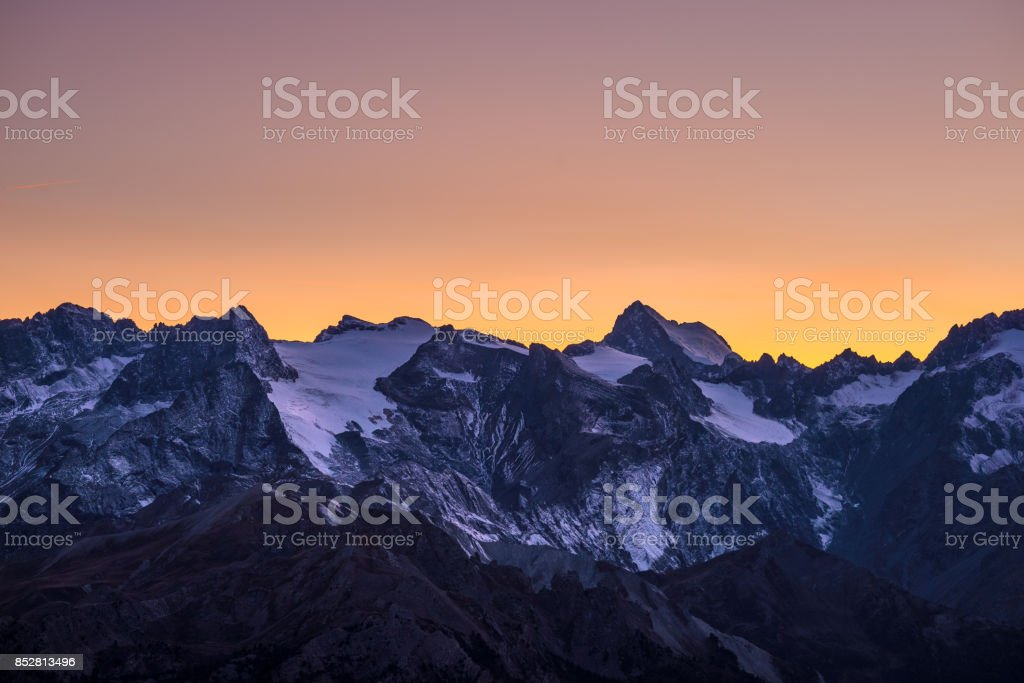 Colorful sky at dusk beyond the glaciers on the majestic peaks of the Massif des Ecrins (4101 m), France. Telephoto view from distant at high altitude. Clear orange sky. stock photo