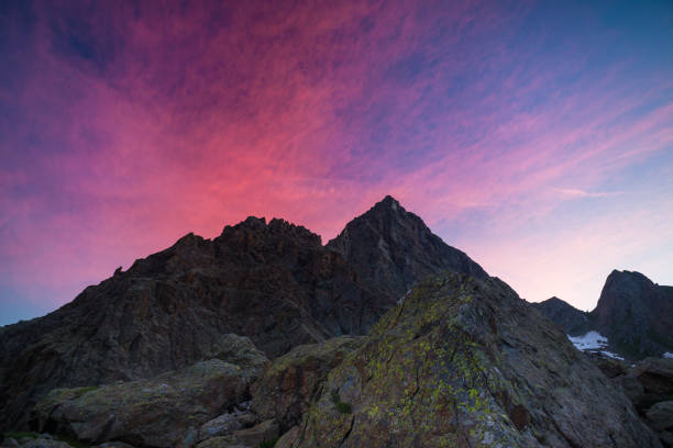 colorful sky beyond rocky mountain peak on the italian alps at dusk. - courmayeur estate foto e immagini stock