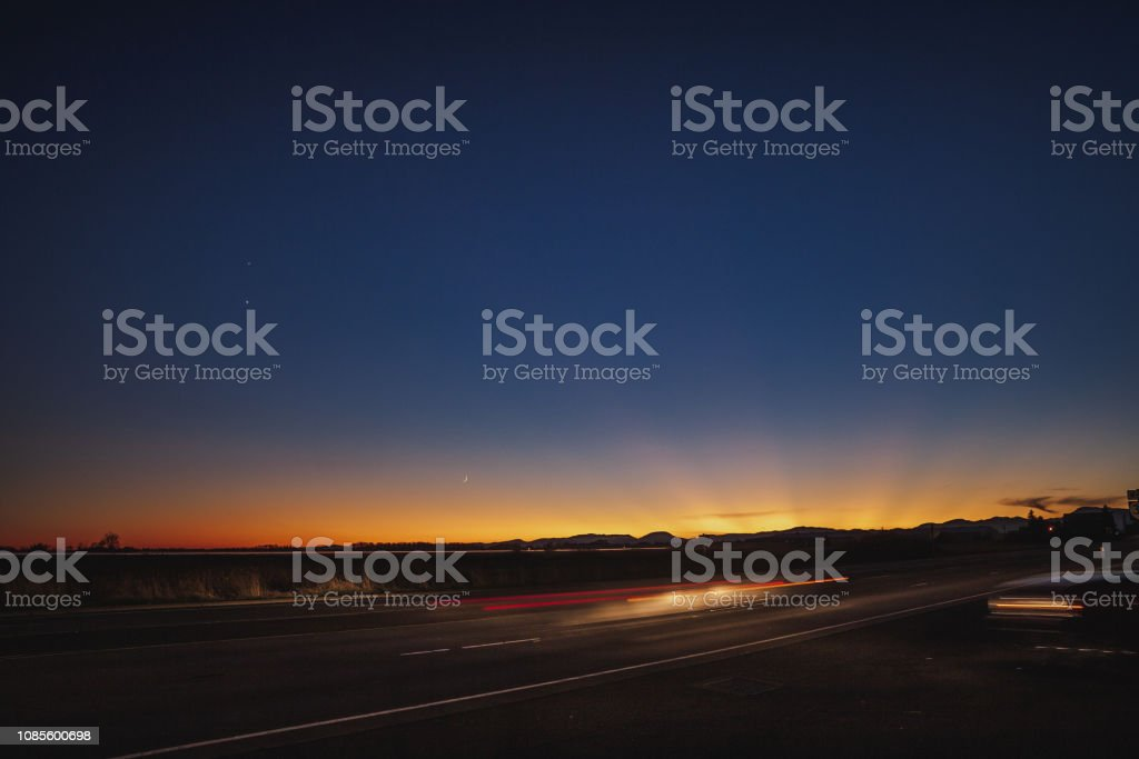 Beautiful sunset and blurred headlights of a car driving down a...
