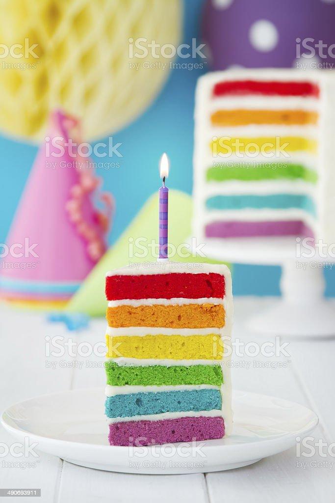 Colorful slice of rainbow birthday cake stock photo