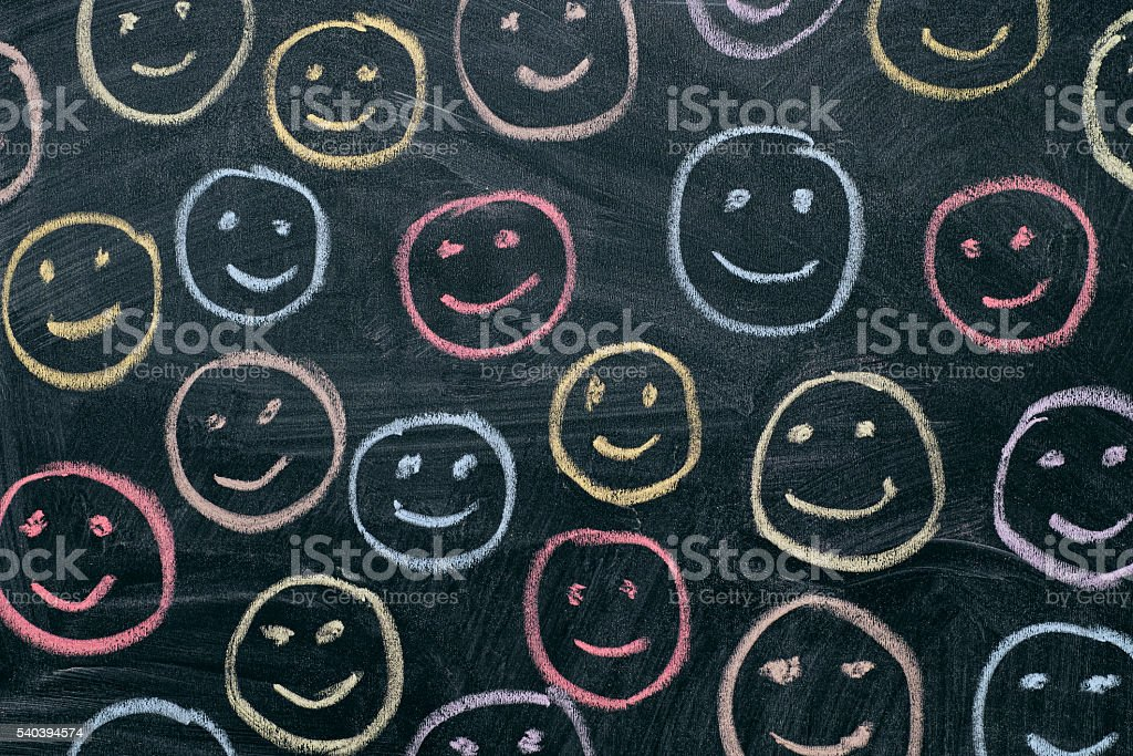 Colorful smileys on chalkboard background stock photo