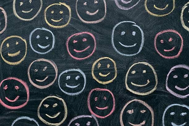 colorful smileys on chalkboard background - smiley face stock photos and pictures