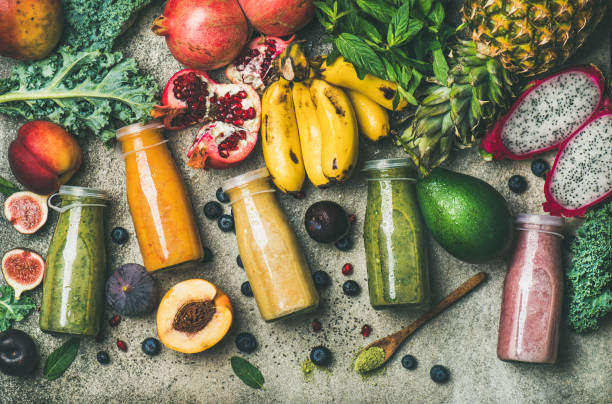 Colorful smoothies in bottles with fresh tropical fruit and superfoods stock photo