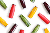 Colorful smoothies in glass bottles isolated on white background, top view.
