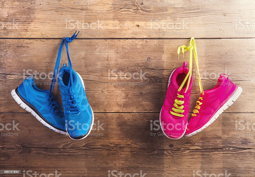 Colorful sneakers hanging on a wall by their laces stock photo