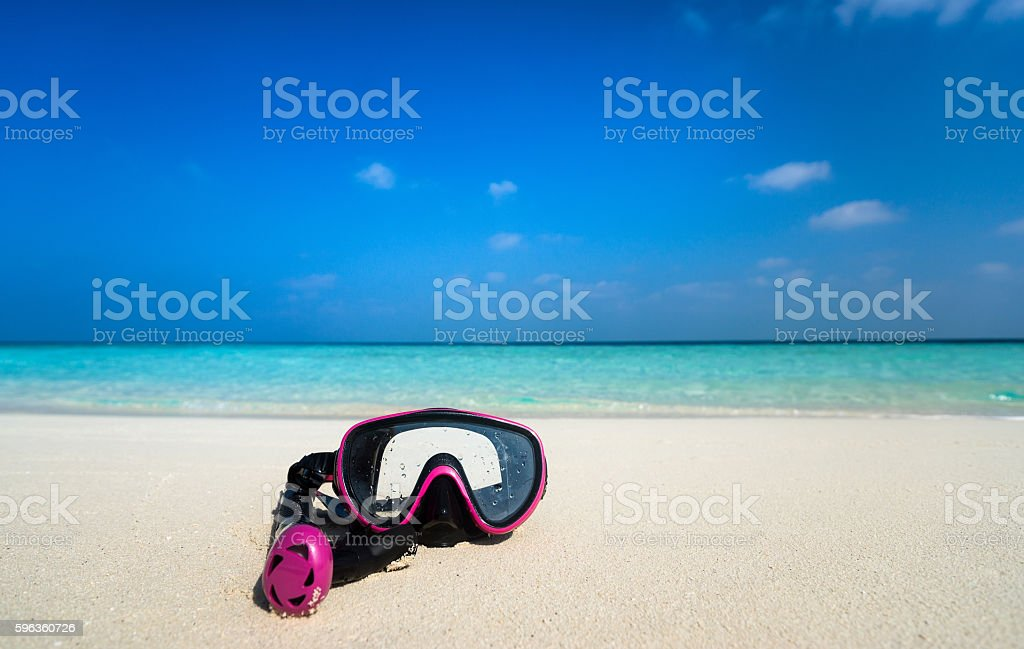 Colorful snorkel mask by the sea, remote tropical beaches. royalty-free stock photo