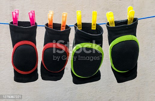 Colorful soaked knee pads attached on nylon wire for drying after wash.