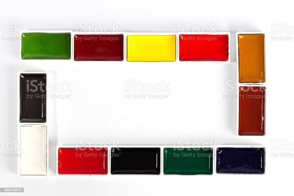 b38d9bf244e9 Colorful solid watercolor pans set making a frame with copy space on white  background - Stock image .