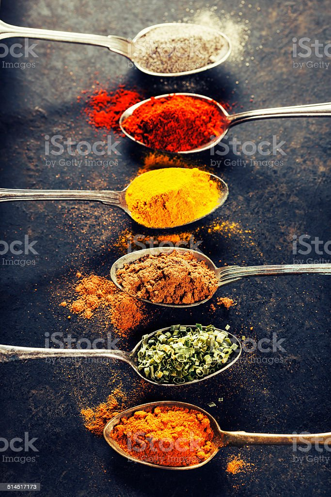 Colorful spices in metal spoons stock photo