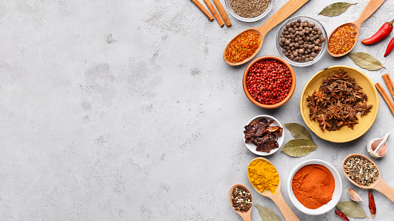 Colorful spices in spoons and bowls with fresh seasoning on grey background, top view, copy space