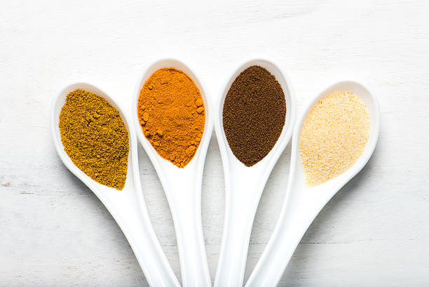 colorful spices in spoons stock photo