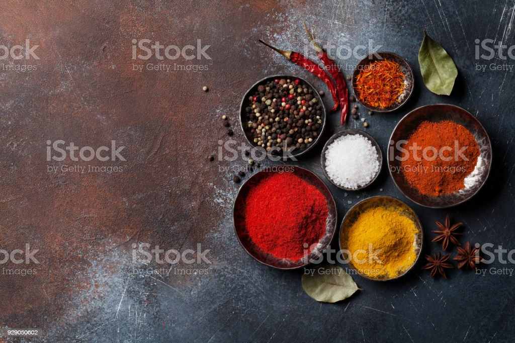 Colorful spices on stone table stock photo