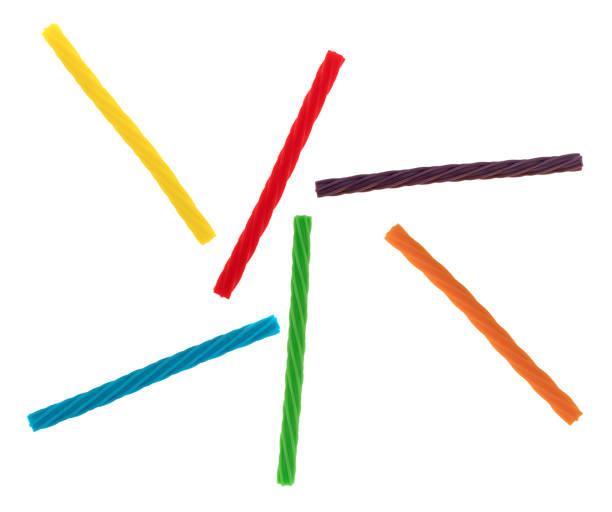 colorful spiral licorice sticks on a white background - liquirizia foto e immagini stock