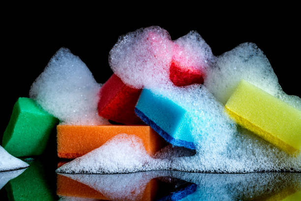 colorful sponges with foam and reflection isolated on black background - spugna per le pulizie foto e immagini stock