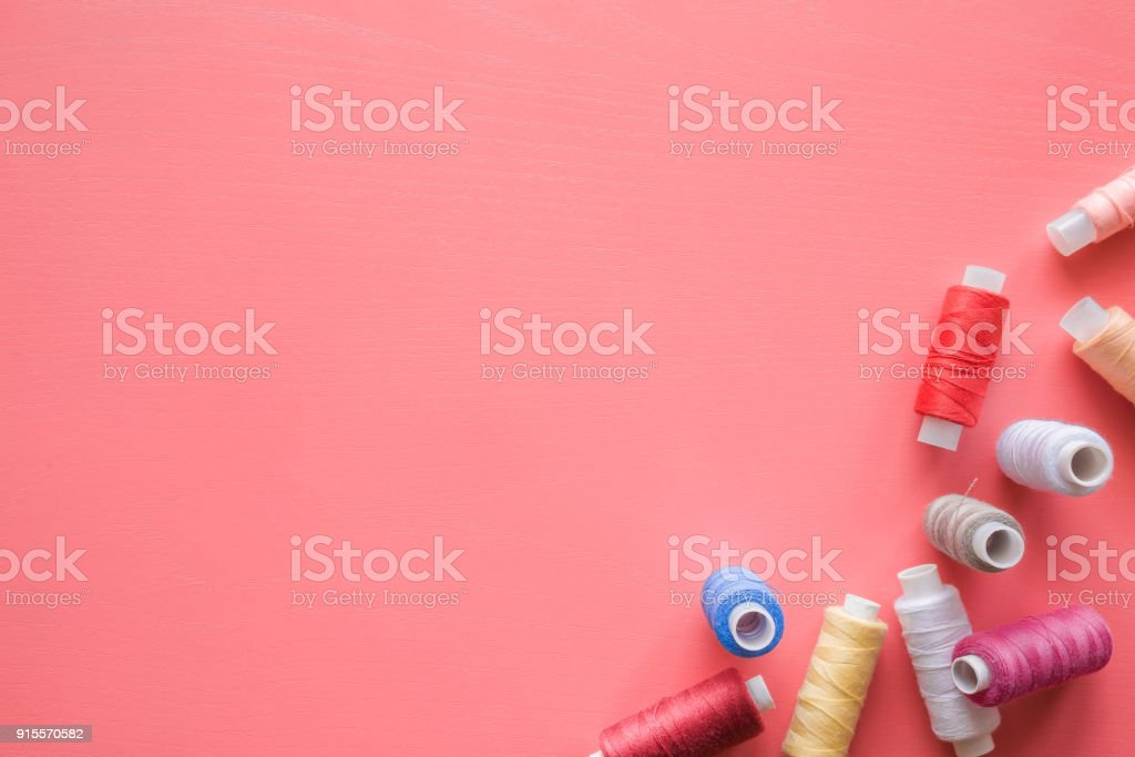 Colorful spools of threads on the pastel pink background. Mock up for dressmakers or textile shops offers as advertising or other ideas. Womanly hobby. Sewing concept. Empty place for text or a logo. stock photo