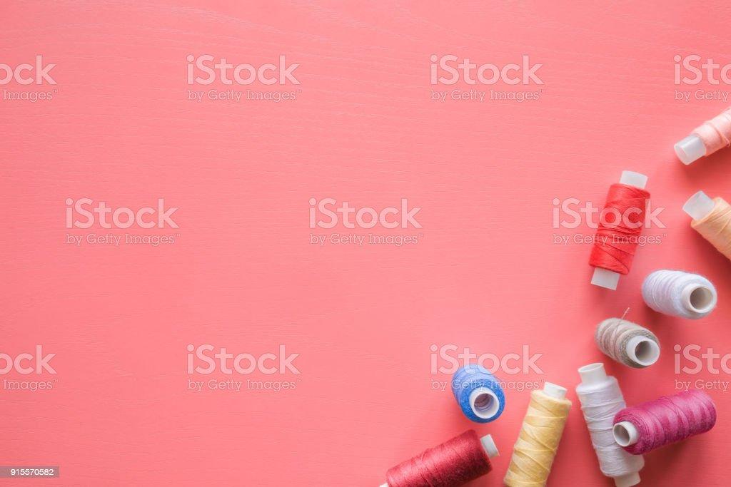 Bobines colorés de discussions sur le fond rose pastel. Maquette pour couturières ou les magasins de textiles offres comme de la publicité ou autres idées. Hobby féminine. Notion de couture. Place vide pour du texte ou un logo. - Photo